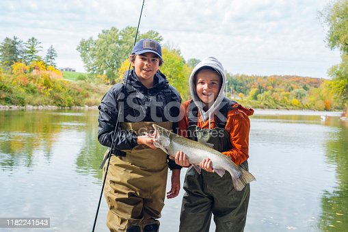 Two young fisherman holding a freshly caught rainbow trout or Steelhead on a fall day.