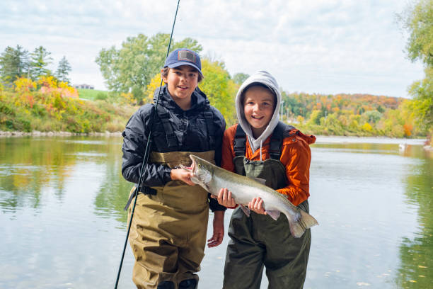 Brothers holding a freshly caught rainbow trout or steelhead on a fall day. stock photo