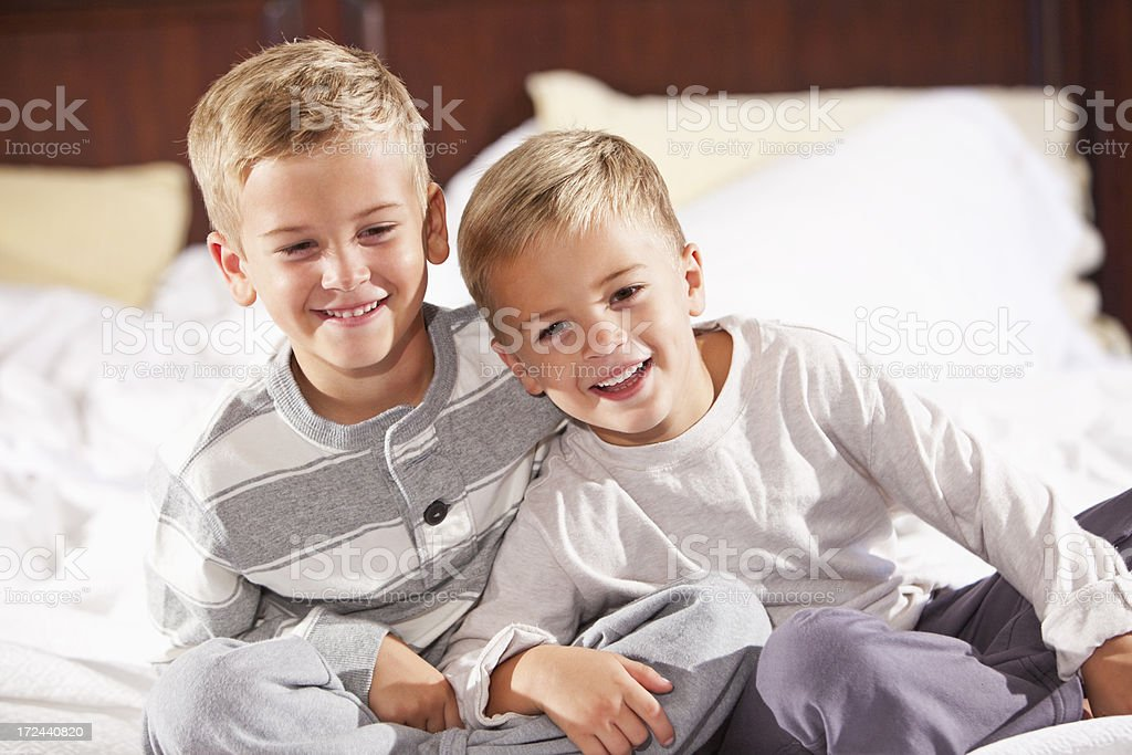 Brothers laughing, sitting on bed stock photo