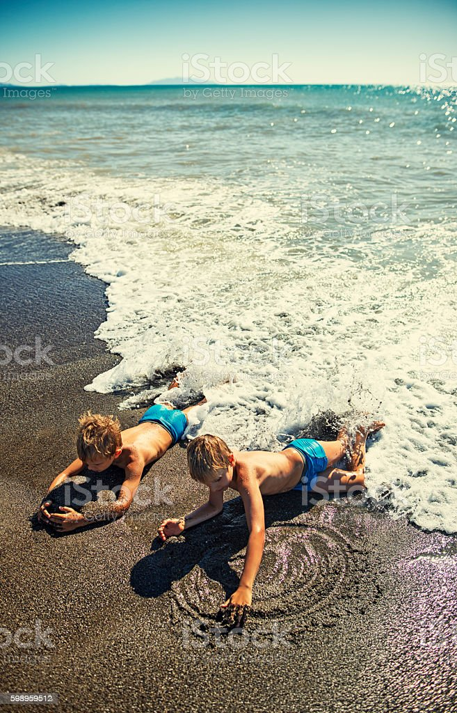 Brothers lying on beach in waves and playing stock photo