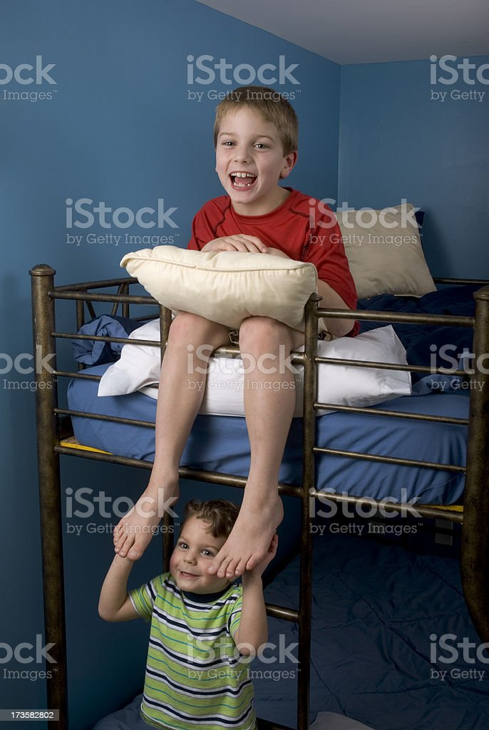Brothers on Bunk Bed Tickling Feet Facing Forward stock photo