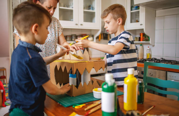 Brothers painting a cardboard dinosaur costume stock photo