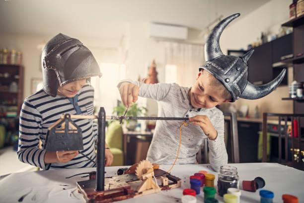 brüder, die malerei schulprojekt von trebuchet - kinderteil stock-fotos und bilder