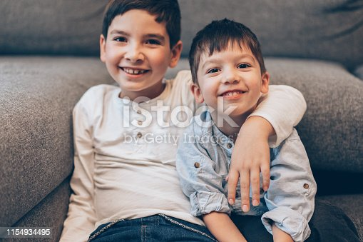 Portrait of Two smiling boys, brothers sitting on the floor at home and looking at camera
