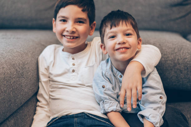 Brothers Portrait of Two smiling boys, brothers sitting on the floor at home and looking at camera brother stock pictures, royalty-free photos & images