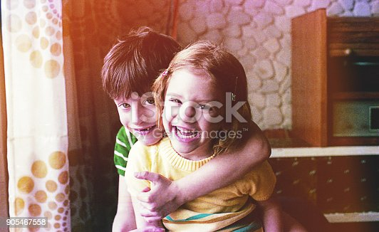 Vintage image of a girl and boy brothers playing at home