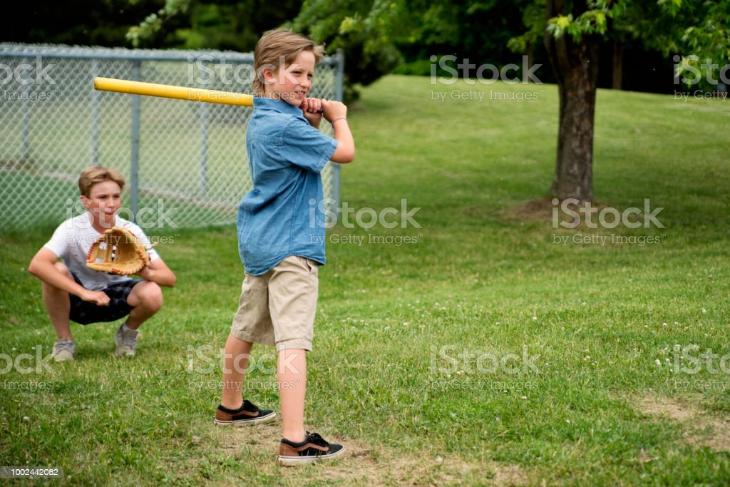 Brothers playing baseball in suburb park. stock photo