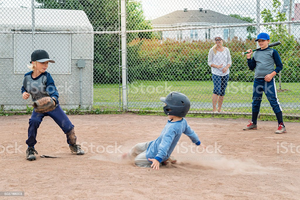 Brothers playing baseball, one sliding to the plate mom watching. stock photo