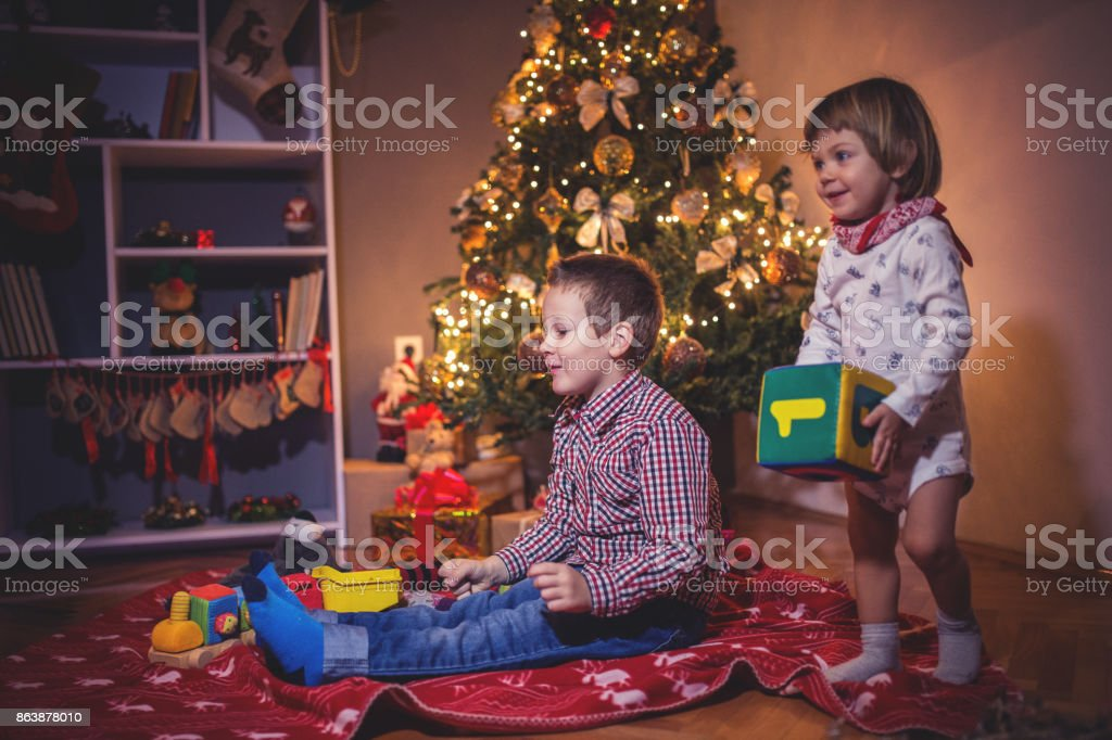 Brothers playing by the Christmas tree stock photo