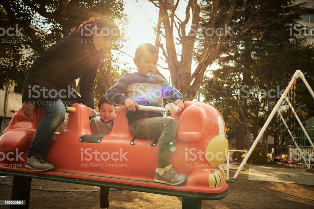 Brothers playing in park at the evening - Royalty-free Adult Stock Photo