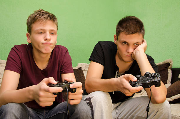 Brothers playing video games boredom stock photo