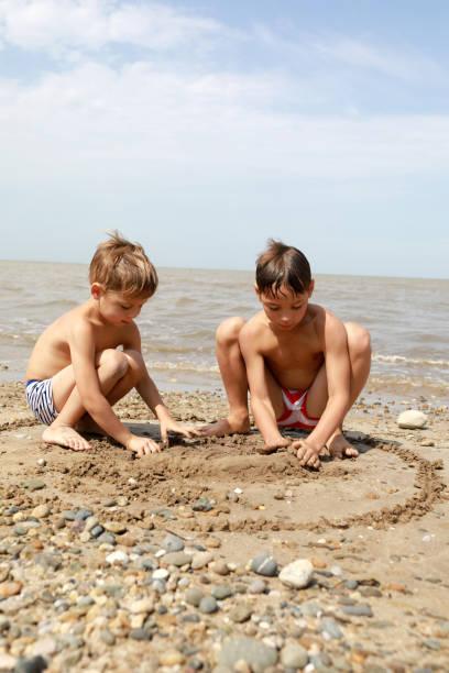 Hermanos jugando con guijarros en la playa - foto de stock