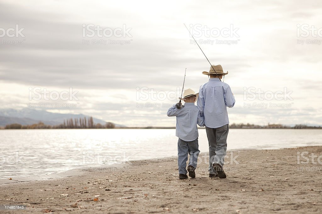 Brothers Wearing Cowboy Hats Walking on Beach with Fishing Poles royalty-free stock photo