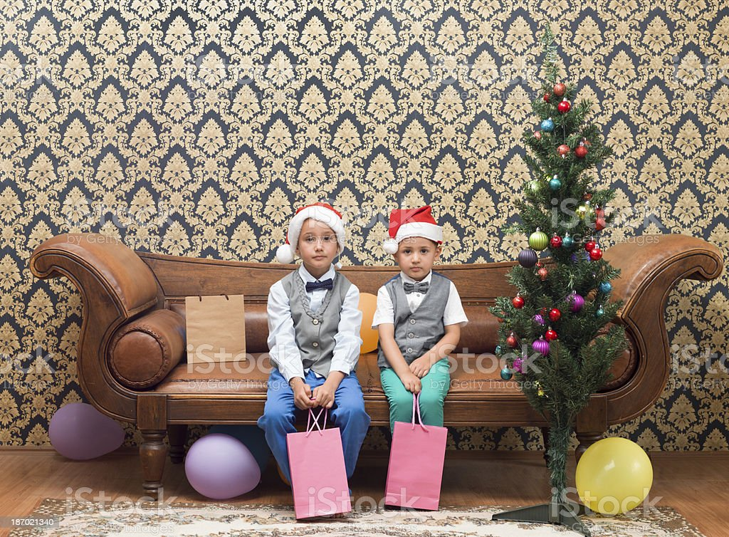 Brothers wearing Santa hat sitting on sofa with gifts royalty-free stock photo