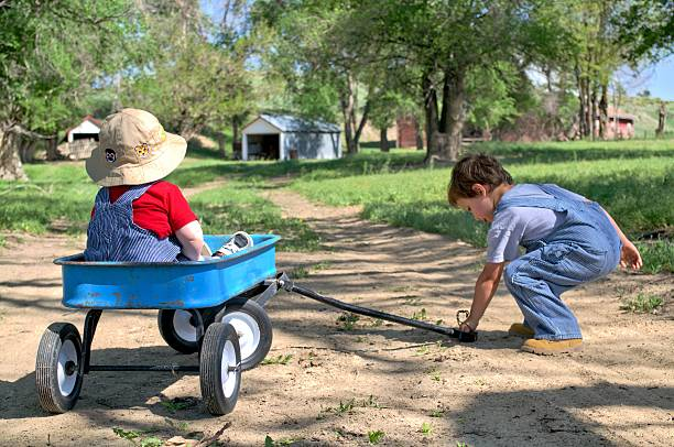 brothers with a wagon brothers playing with a toy wagon outside bib overalls boy stock pictures, royalty-free photos & images