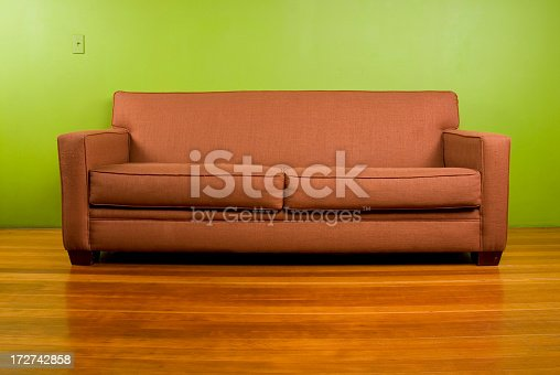 A vintage couch sits in a green room.