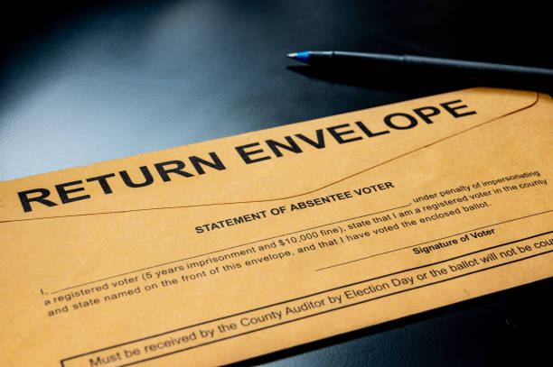 brown absentee ballot return envelope on a black desk with ink pen Absentee voting material typically sent to voters for elections absentee stock pictures, royalty-free photos & images
