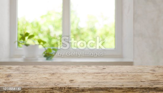 885452818istockphoto Brown aged wooden tabletop with blurred window for product display 1014658130