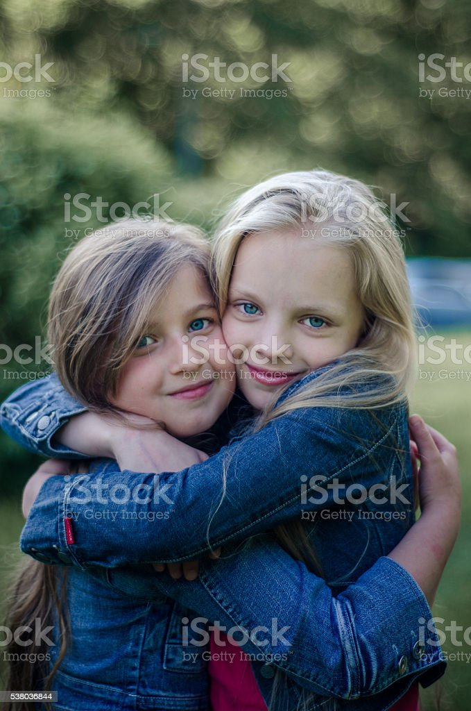 Brown and blond haired cute little girls friends smiling. – Foto