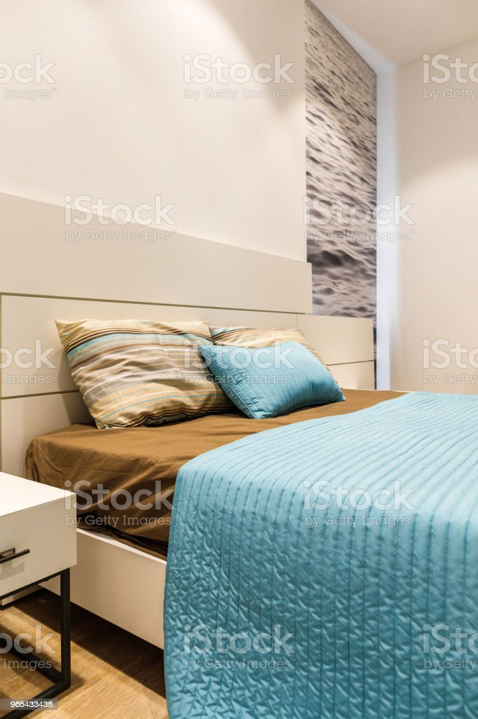 Brown and blue bedclothes on bed in modern bedroom zbiór zdjęć royalty-free