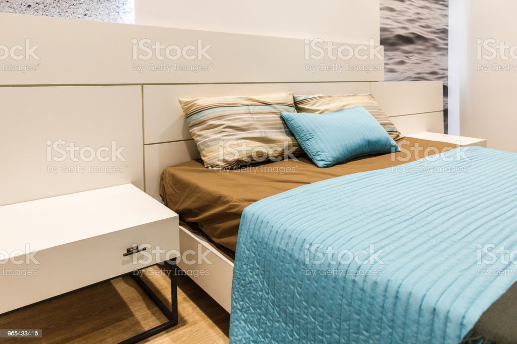 Brown and blue linens on bed in cozy bedroom zbiór zdjęć royalty-free