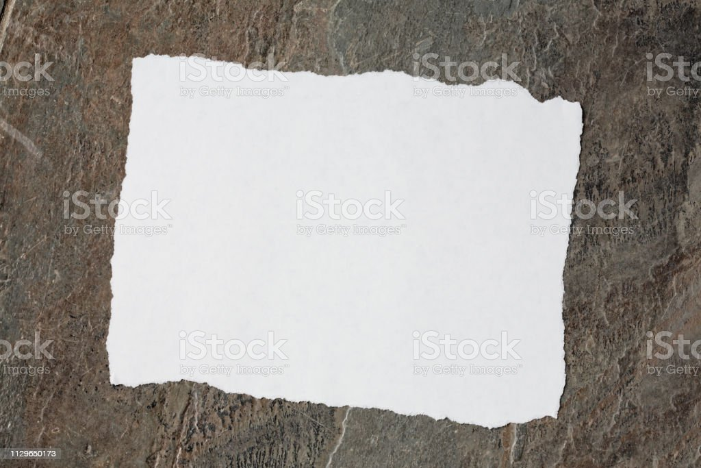 Brown and gray slate background with torn white paper stock photo