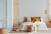Brown and orange pillows on white bed in natural bedroom interior with wicker lamp and wooden bedside table with vase