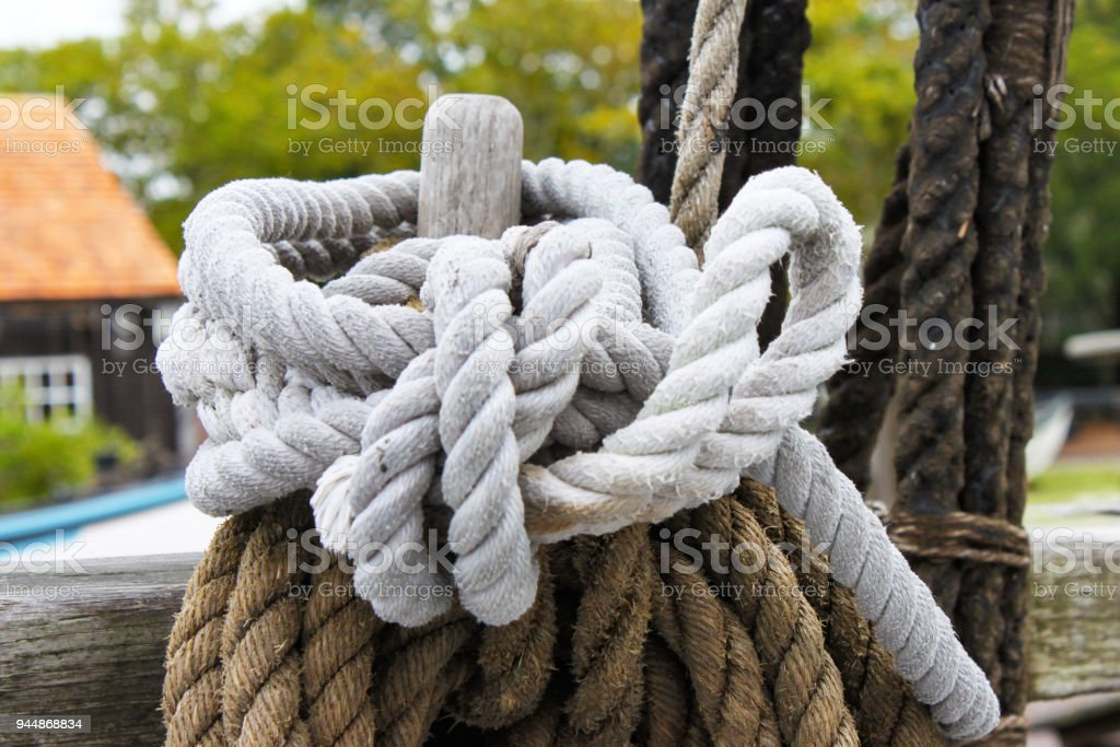 Brown and white braided ropes tied around a post at a marina - selective focus with bokeh background stock photo