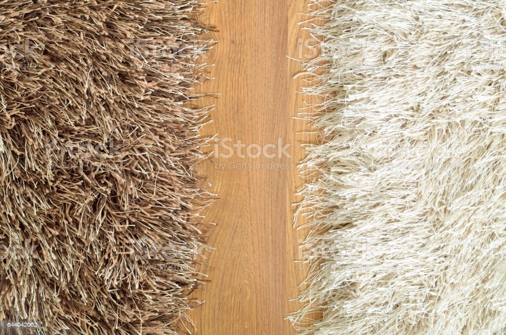 Brown and white hairy carpets divide in half and floor stock photo