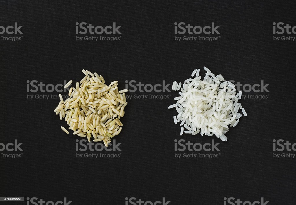 Brown and white rice on black stock photo