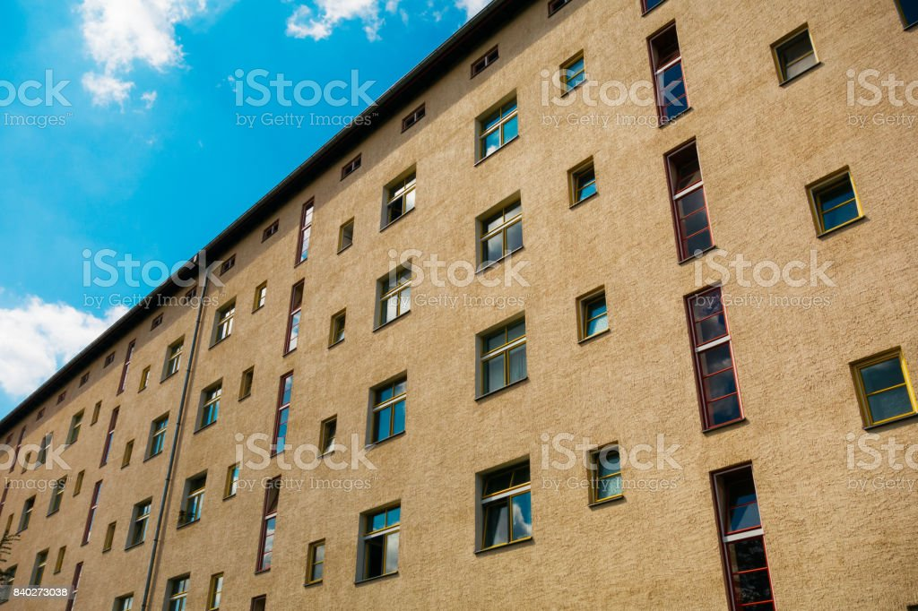 brown apartment building with small windows stock photo