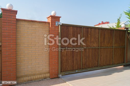 istock Brown automatic wooden gates of private house. Inside view 872497104