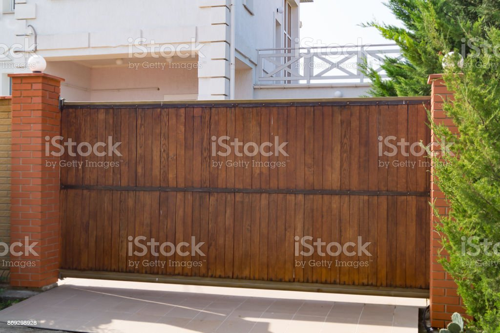 Brown automatic wooden gates of private house stock photo