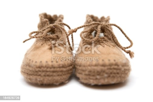 Pair of brown leather booties isolated on a white background. Shallow depth of field. Focus on shoelaces.