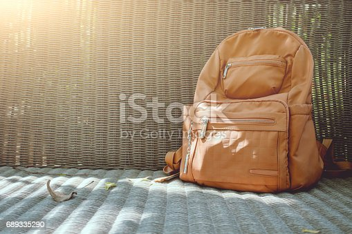 istock Brown backpack on wicker chair 689335290