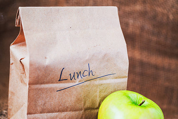 Brown bag lunch with apple stock photo