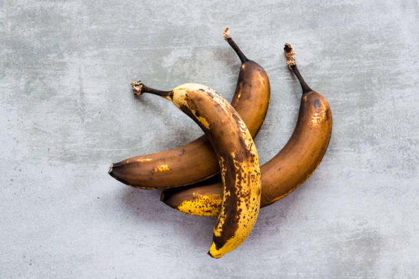 brown bananas on a concrete table - ripe stock photos and pictures