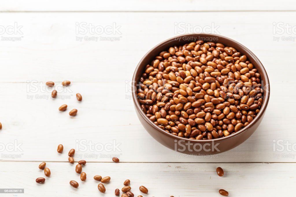 brown beans in a plate on a wooden background, top view royalty-free stock photo