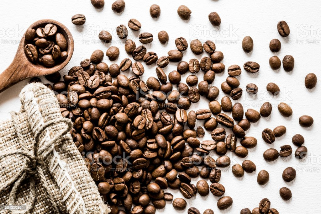 Brown beans with burlap bag and wooden spoon on the white table. Harvest of coffee in different countries. Choice of the best sort and quality coffee. stock photo