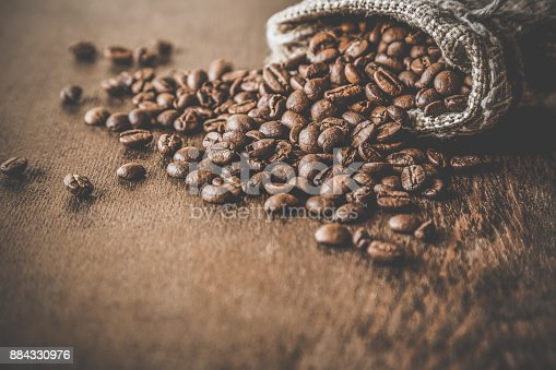 istock Brown beans with burlap bag on the wooden table. Harvest of coffee in different countries. Choice of the best sort and quality coffee. Rustic atmosphere. Advertising concept. 884330976