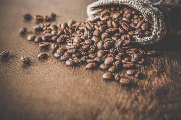 나무 테이블에 삼 베 가방으로 갈색 콩. 다른 나라에서 커피의 추수입니다. 최고의 정렬 및 품질 커피의 선택입니다. 소박한 분위기입니다. 광고 개념입니다. - coffee 뉴스 사진 이미지