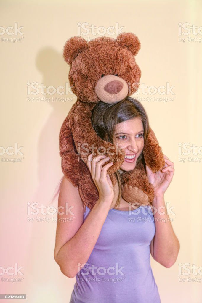 Brown bear carried piggyback by smiling Russian indoor girl model stock photo