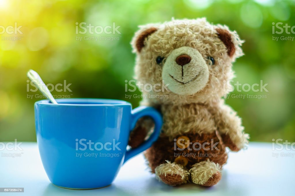 Brown bear doll sitting with a cup of coffee on blurred green natural...