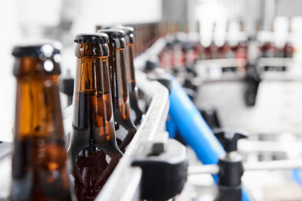 Brown beer bottles at a production line stock photo