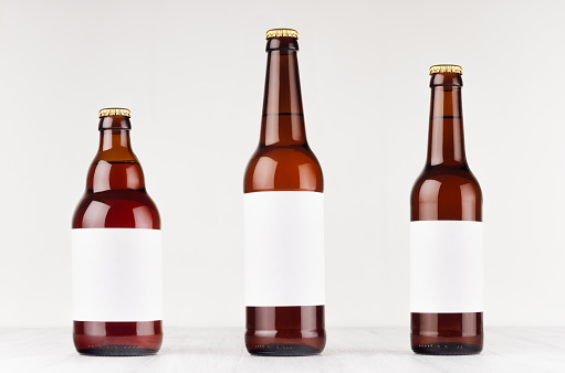Brown beer bottles collection different type with blank white label on white wooden board, mock up.