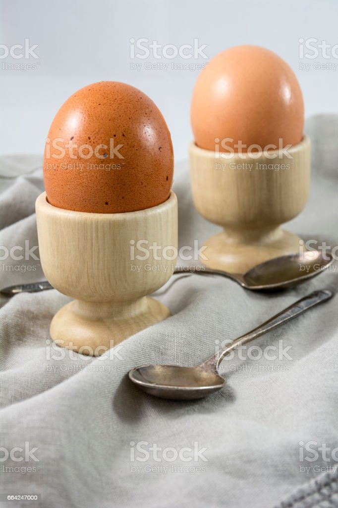 Brown boiled eggs in egg cups with spoons stock photo