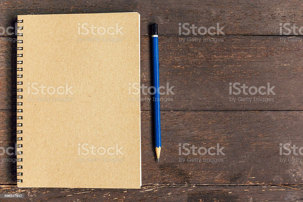 brown book and pencil on wood table background with space Lizenzfreies stock-foto