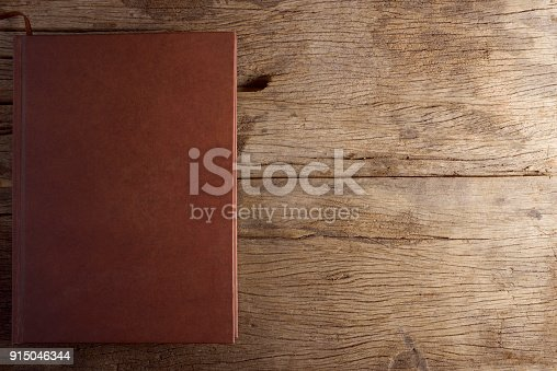 istock Brown book on wooden table. 915046344