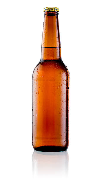 brown bottle of beer with drops on a white background - dark beer stock photos and pictures
