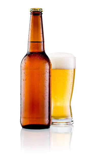 Brown bottle with drops and Glass of beer isolated Brown bottle with drops and Glass of beer isolated on a white background bitter ale stock pictures, royalty-free photos & images
